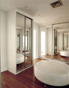 closet organizado branco com espelho no quarto