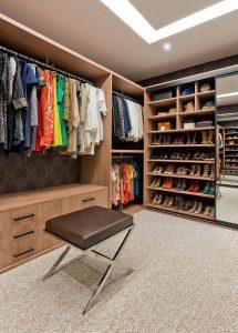 closet organizado de madeira com banqueta para melhorar organizar