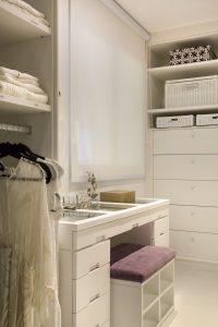 closet organizado com mesa de maquiagem e comoda