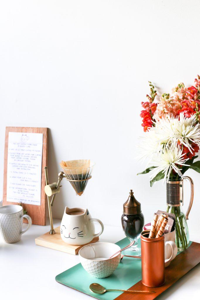 Cantinho do café em cima de aparador decorado com elementos divertidos