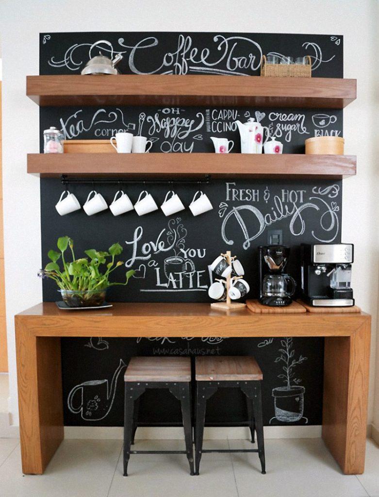 Cantinho do café decorado com bancada, banquetas e prateleiras em madeira.