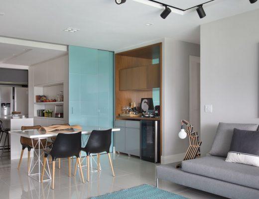 decoração de apartamento pequeno com porta de correr entre a sala e a cozinha