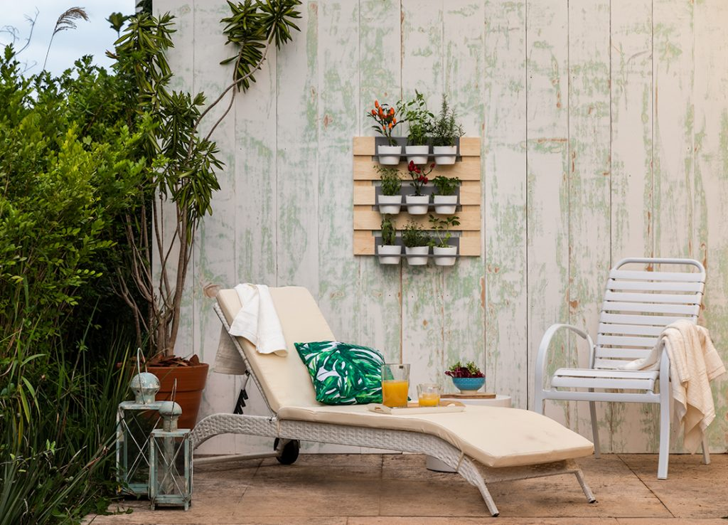 decoração de área externa feita com jardim vertical com suporte de pallets