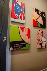 quadros de decoração pop art pendurados próximo a porta